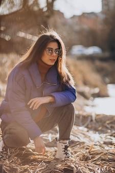 Giovane donna in giacca blu fuori nel parco