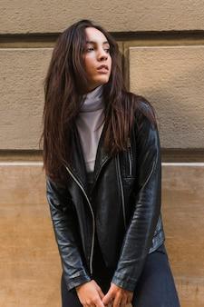 Giovane donna in giacca di pelle nera in piedi contro il muro guardando lontano