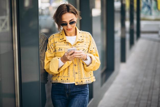Giovane donna in giacca gialla utilizzando il telefono fuori in strada