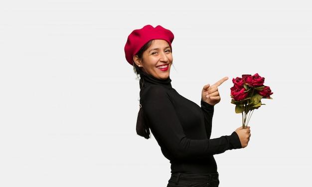 Giovane donna in giorno di san valentino che punta al lato con il dito