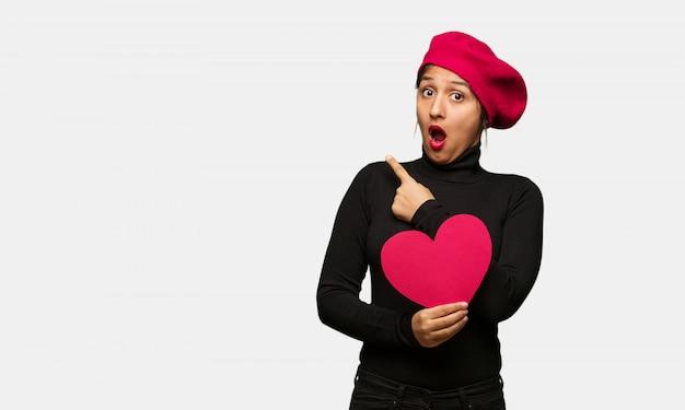 Giovane donna in giorno di san valentino che punta verso il lato