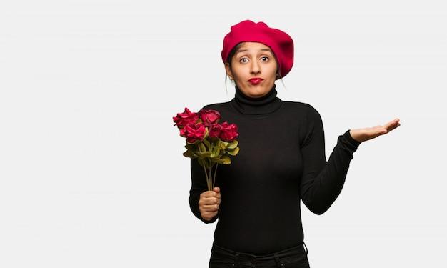 Giovane donna in giorno di san valentino dubitando e alzando le spalle spalle