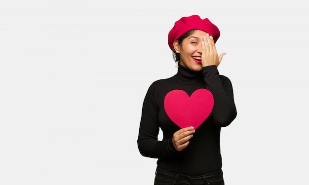 Giovane donna in giorno di san valentino gridando felice e coprendo il viso con la mano