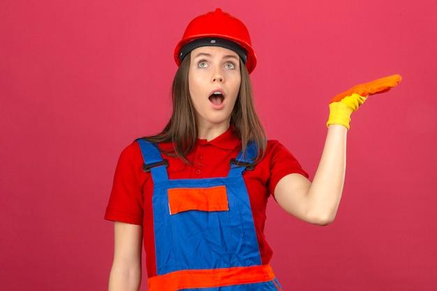 Giovane donna in guanti dell'uniforme della costruzione e casco di sicurezza rosso colpiti dall'espressione di sorpresa che sta con la mano sollevata su fondo rosa scuro