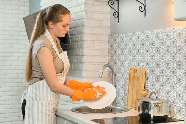 Giovane donna in guanti grembiule lavare i piatti con spugna e detersivo