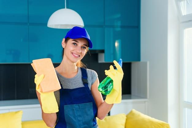 Giovane donna in guanti protettivi che utilizza uno spruzzo e uno straccio mentre pulendo a casa in appartamento. lavori domestici e concetto di pulizia della casa.