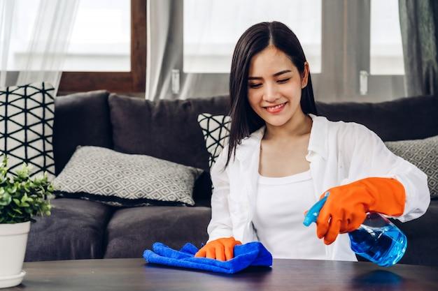 Giovane donna in guanti protettivi facendo uso di uno spruzzo e di uno straccio mentre pulendo a casa nel salone a casa lavoro domestico e concetto di pulizia domestica