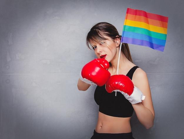 Giovane donna in guantoni da boxe con bandiera lgbt