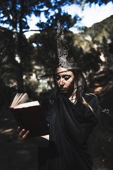 Giovane donna in libro di lettura del costume dello stregone in foresta