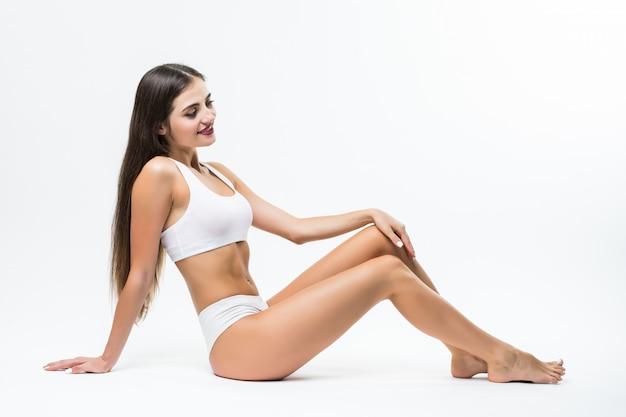 Giovane donna in lingerie nera seduto sul muro grigio. giovane modello femminile caucasico