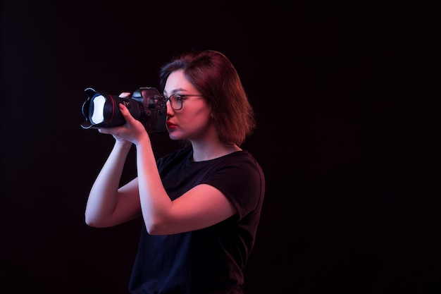 Giovane donna in maglietta nera con la macchina fotografica