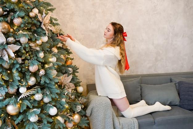 Giovane donna in maglione bianco che decora l'albero di natale a casa