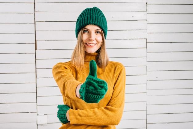 Giovane donna in maglione che mostra pollice in su