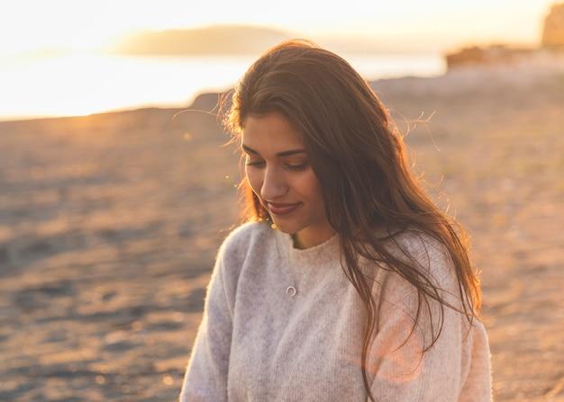 Giovane donna in maglione che si siede sulla riva del mare sabbioso