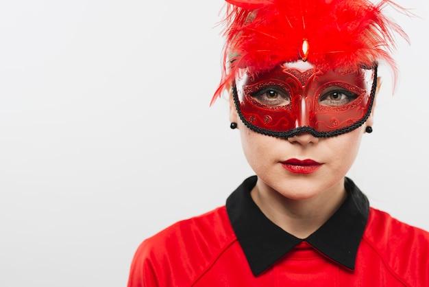 Giovane donna in maschera con piume rosse