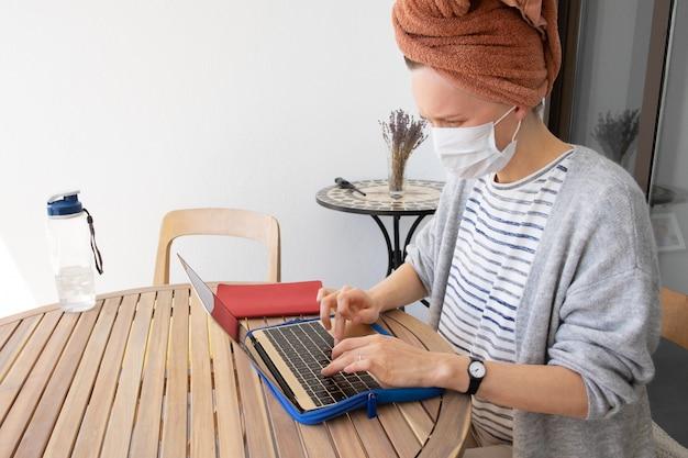 Giovane donna in maschera di medicina e con un asciugamano sulla testa