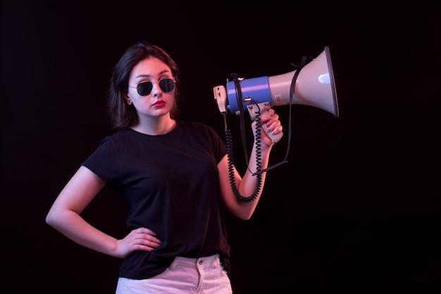 Giovane donna in megafono nero della tenuta della maglietta