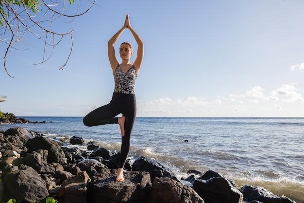 Giovane donna in nero facendo yoga sulla spiaggia di roccia