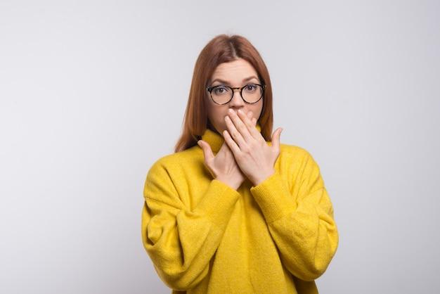 Giovane donna in occhiali chiusura bocca