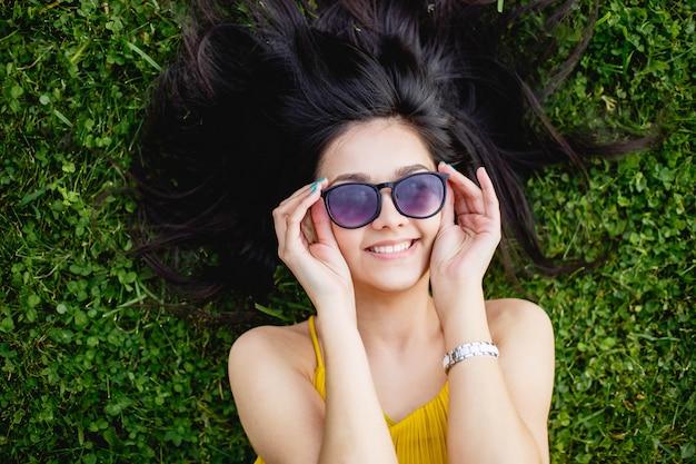 Giovane donna in occhiali da sole che si trova su un prato verde e sorridente, vista dall'alto