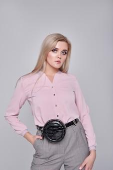 Giovane donna in pantaloni e una camicia rosa. ragazza che posa su una parete grigia. acconciatura. ragazza con una borsetta nera su un treno. foto di moda
