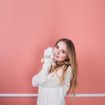Giovane donna in piedi con coniglio carino