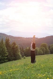 Giovane donna in piedi con un mazzo di fiori e mani sollevate