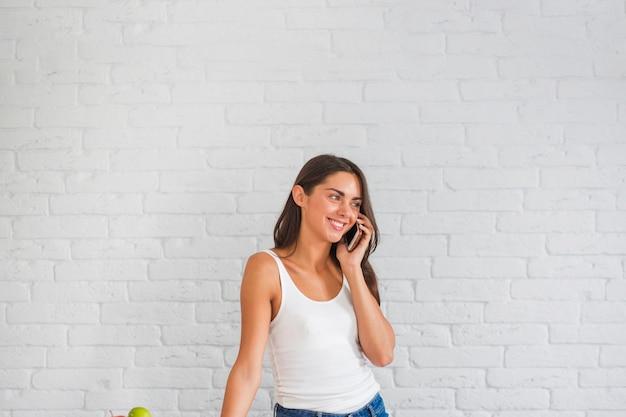 Giovane donna in piedi contro il muro bianco parlando sul cellulare