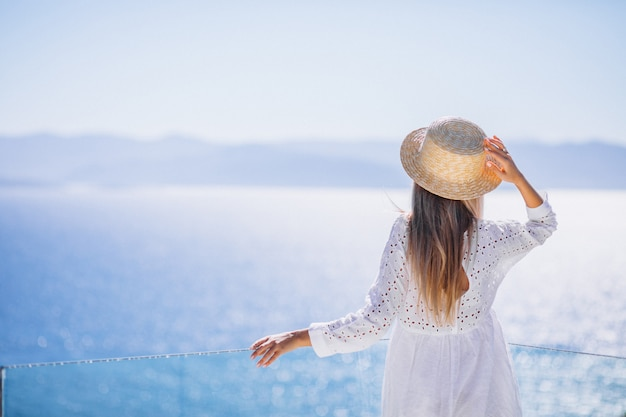 Giovane donna in piedi da dietro e guardando il mare