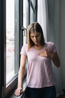 Giovane donna in piedi dalla finestra che soffre di dolore toracico