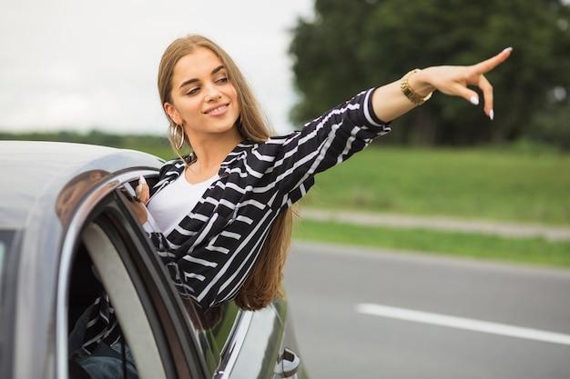 Giovane donna in piedi fuori dal finestrino della macchina che punta a qualcosa