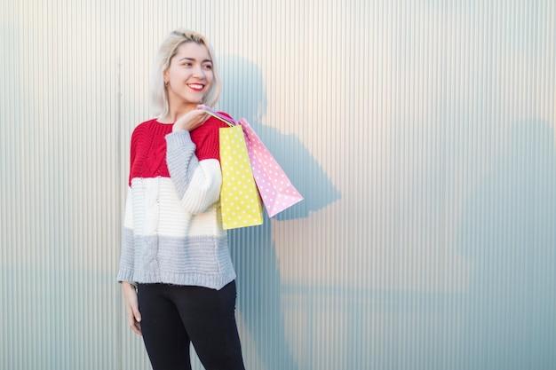 Giovane donna in piedi in un centro commerciale mentre distoglie lo sguardo