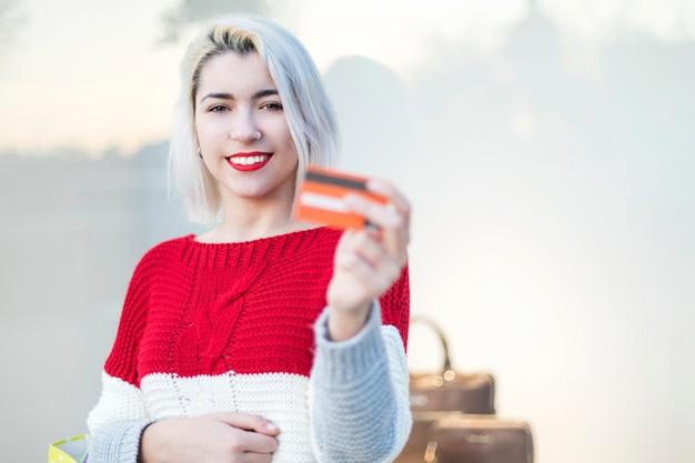 Giovane donna in piedi in un centro commerciale mentre si tiene una carta di credito
