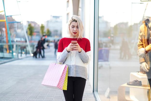 Giovane donna in piedi in un centro commerciale mentre si utilizza un telefono cellulare