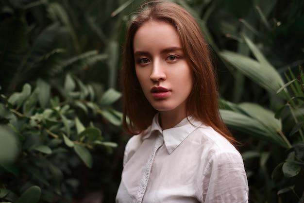 Giovane donna in piedi in una serra