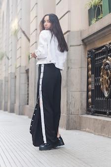 Giovane donna in piedi sul marciapiede guardando oltre la spalla