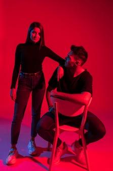 Giovane donna in piedi vicino a uomo sulla sedia