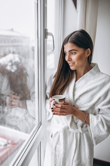 Giovane donna in piedi vicino alla finestra che beve caffè caldo