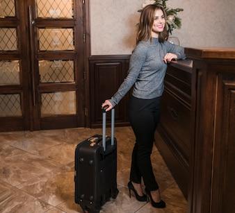 Giovane donna in piedi vicino alla reception con la valigia in hotel