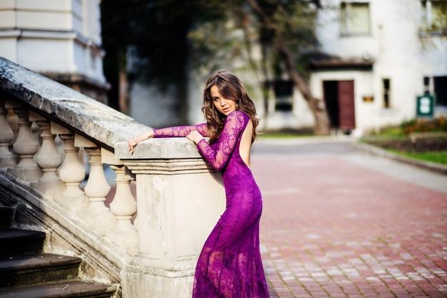Giovane donna in piedi vicino alle mura di un antico tsastle bella volossya. ragazza di bellezza all'aperto nell'antico castello. ragazza bellissima modella in abito lungo. bruna godendo il viaggio. donna felice