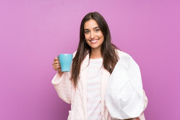 Giovane donna in pigiama e vestaglia sopra la parete viola isolata che tiene una tazza di caffè