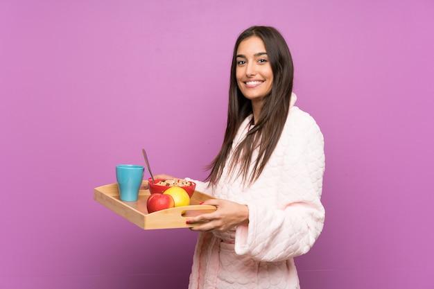 Giovane donna in pigiama e vestaglia sopra la parete viola isolata