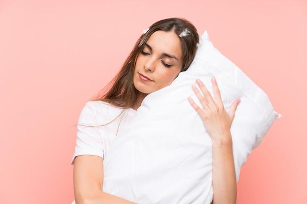 Giovane donna in pigiama sopra la parete rosa isolata