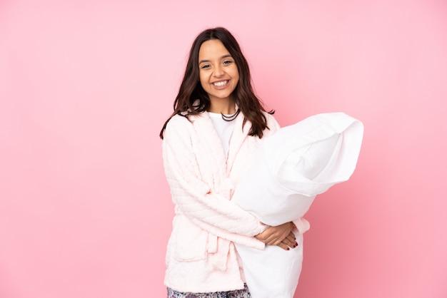 Giovane donna in pigiama sul muro rosa mantenendo le braccia incrociate in posizione frontale