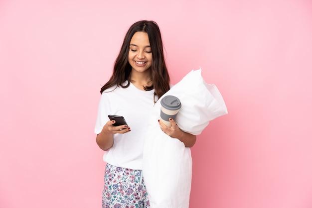 Giovane donna in pigiama sul muro rosa tenendo il caffè da portare via e un cellulare