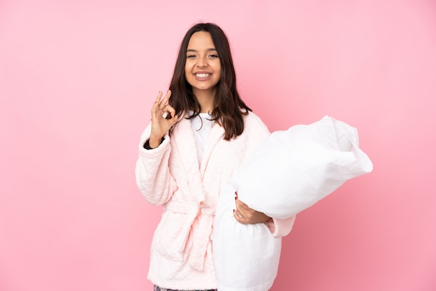 Giovane donna in pigiama sulla parete rosa che mostra un segno giusto con le dita