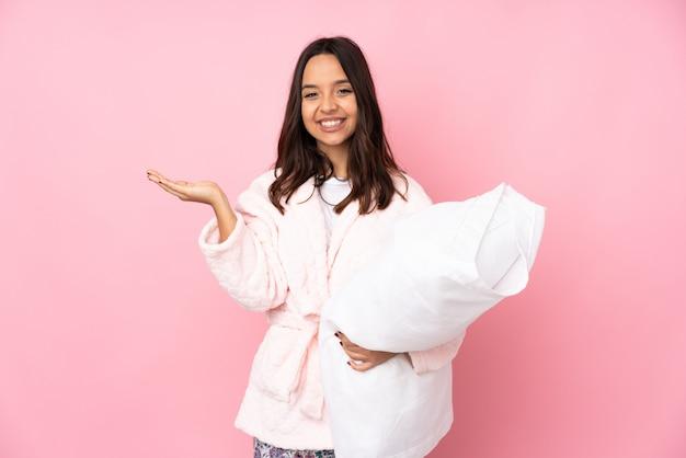 Giovane donna in pigiama sulla parete rosa che tiene immaginario spazio vuoto sul palmo