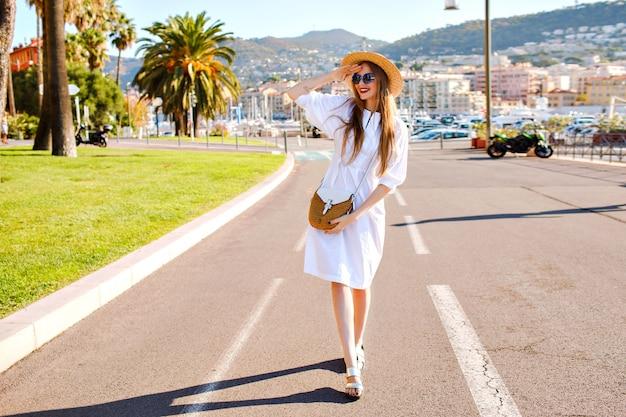 Giovane donna in posa e indossa un abito femminile elegante alla moda e accessori di paglia