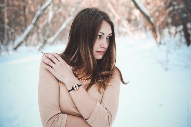 Giovane donna in posa in inverno nella foresta
