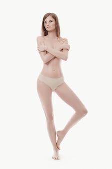 Giovane donna in posa in topless, pelle perfetta